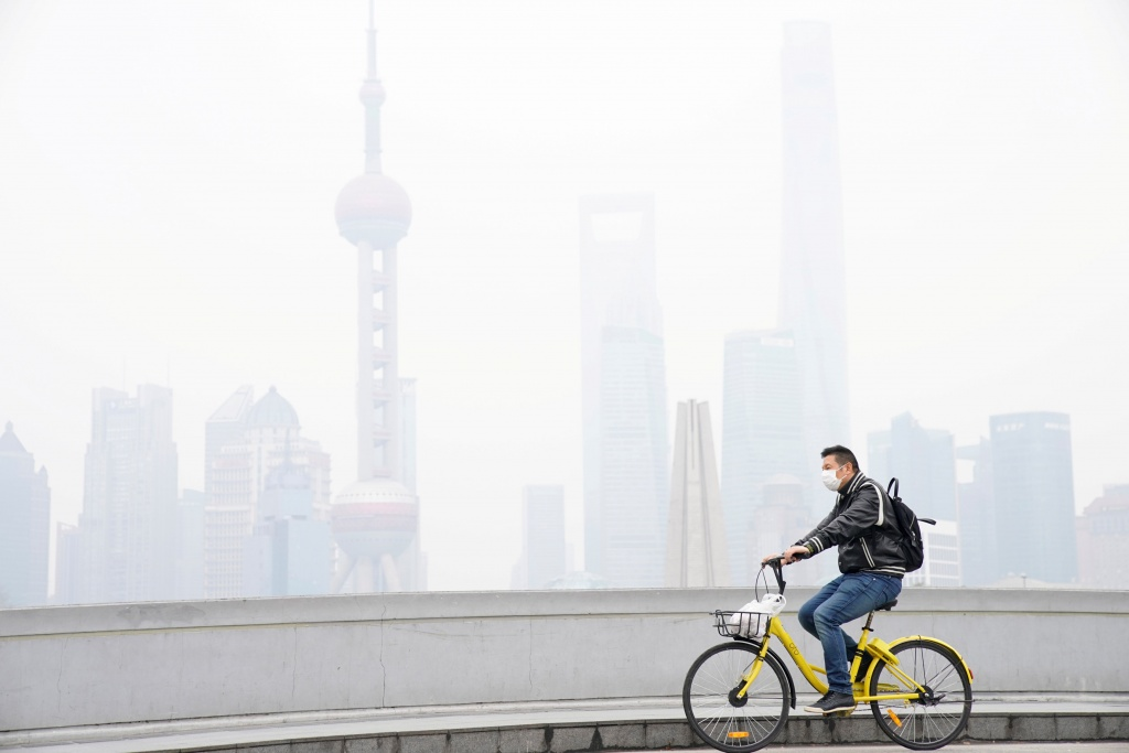 Man wearing a face mask rides a bicycle on a bridge in front of the financial district of Pudong covered in smog during a polluted day in Shanghai