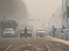 Pedestrians cross a road amidst smog on a polluted day in Nanjing