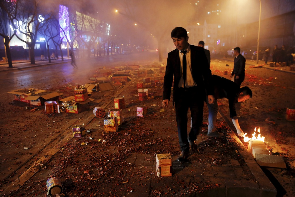 People make sure that all firecrackers and fireworks have exploded during celebrations for the start of the Chinese Lunar New Year of Monkey in Beijing
