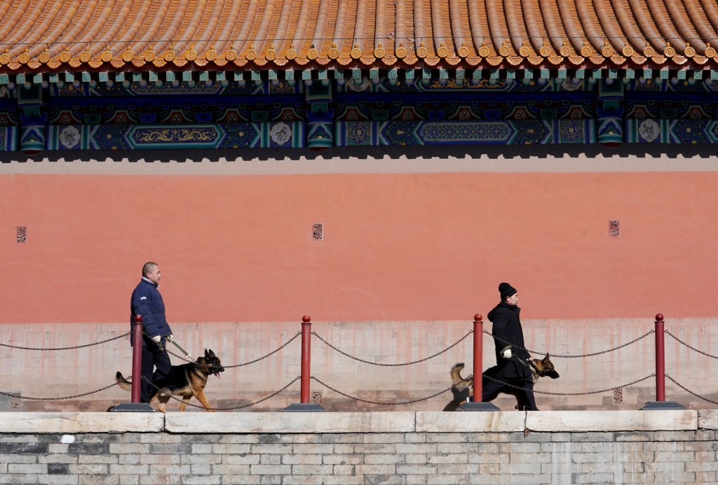 Security staff of canine patrol squad Zhang Yu and Chang Fumao patrol with guard dogs at the Forbidden City in central Beijing