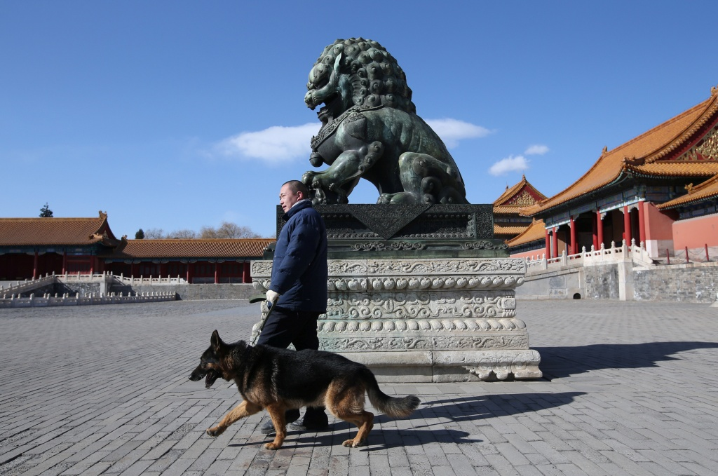 Security staff of canine patrol squad Zhang Yu and a guard dog patrol at the Forbidden City in central Beijing