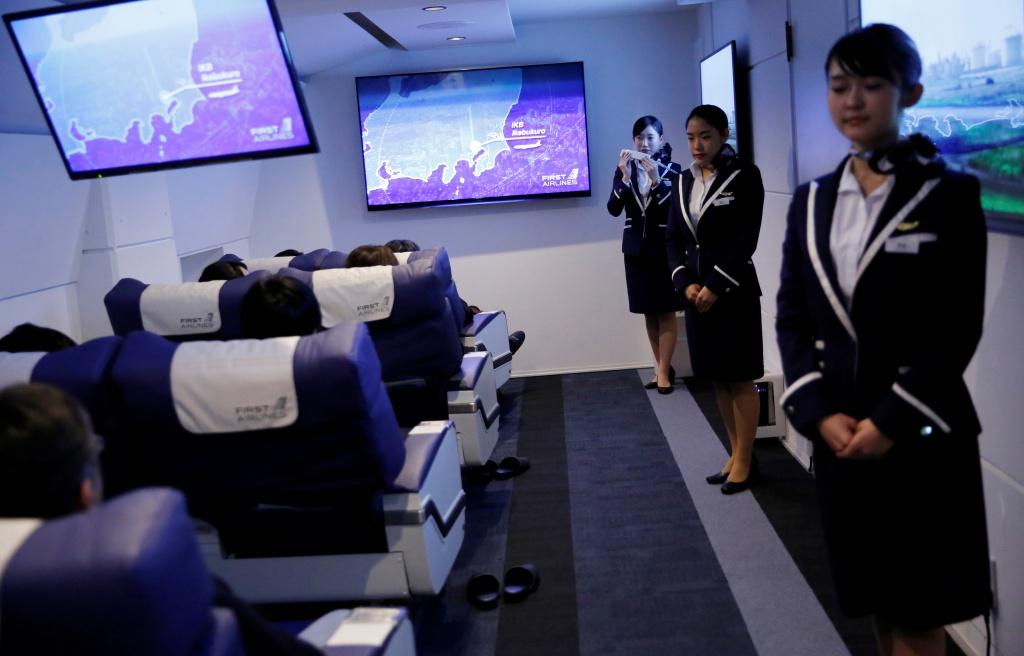 "Staff dressed as flight attendants, greet guests at the ""First Airlines"", virtual first-class airline experience facility in Tokyo"