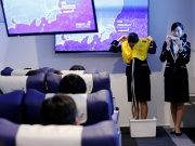 "Staff dressed as flight attendants, perform a safety demonstration at the ""First Airlines"", virtual first-class airline experience facility in Tokyo"