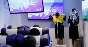 """Staff dressed as flight attendants, perform a safety demonstration at the """"First Airlines"""", virtual first-class airline experience facility in Tokyo"""
