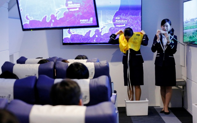 Staff dressed as flight attendants, perform a safety demonstration at the