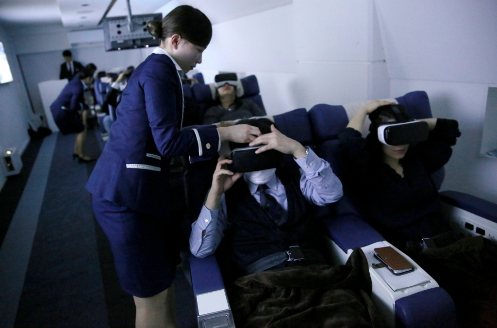 "Staff dressed as flight attendants, help guests to wear VR goggles at the ""First Airlines"", virtual first-class airline experience facility in Tokyo"