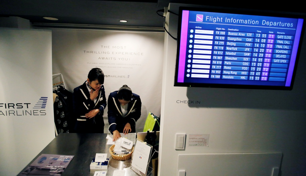 "Staff dressed as flight attendants, work at the ""First Airlines"", virtual first-class airline experience facility in Tokyo"