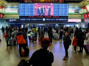 People watch the CCTV Spring Festival Gala TV show on a screen at the Beijing West train station in Beijing