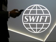 A man using a mobile phone passes the logo of global secure financial messaging services cooperative SWIFT at the SIBOS banking and financial conference in Toronto