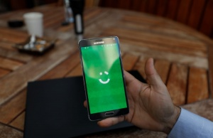 Employee shows the logo of Careem on his mobile in his office in the West Bank city of Ramallah