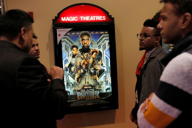 A group of men gather in front of a poster advertising the film