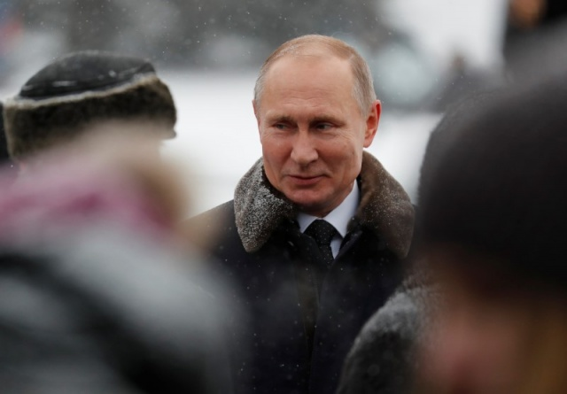 Russian President Vladimir Putin attends a flower-laying ceremony at the Piskaryovskoye Memorial Cemetery to mark the 75th anniversary of the breakthrough the Nazi Siege of Leningrad in the World War II, in St. Petersburg