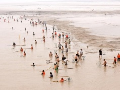 People fish along the bank of the Yellow River as the Sammenxia Dam discharges flood waters downstream, in Pinglu