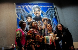 """A group of women pose for a photo in front of a poster advertising the film """"Black Panther"""" on its opening night of screenings at the AMC Magic Johnson Harlem 9 cinemas in Manhattan"""