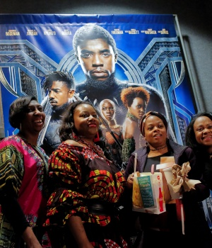 "A group of women pose for a photo in front of a poster advertising the film ""Black Panther"" on its opening night of screenings at the AMC Magic Johnson Harlem 9 cinemas in Manhattan"