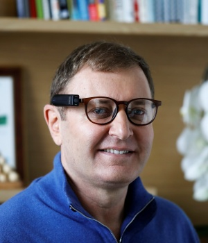 Ziv Aviram, CEO and co-founder of OrCam, poses for a portrait wearing the OrCam MyEye 2.0 device attached to a pair of glasses in his office in Jerusalem