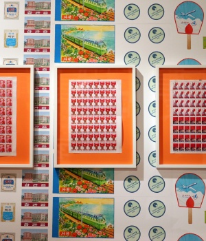 A visitor looks at stamp sheets on display at the 'Made in North Korea: Everyday Graphics from the DPRK' exhibition in London