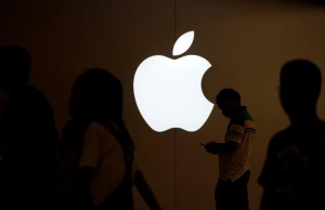 A man looks at the screen of his mobile phone in front of an Apple logo outside its store in Shanghai