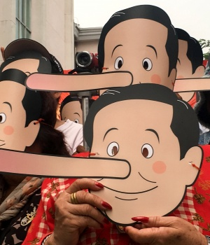 Pro-democracy activists wearing masks mock Thailand's Prime Minister Prayuth Chan-ocha as Pinocchio during a protest against junta at a university in Bangkok