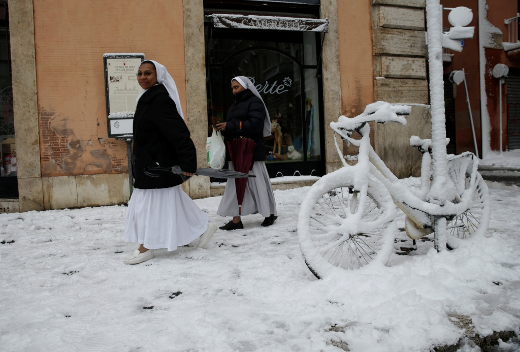 Nuns walk past a bike covered in snow during a heavy snowfall in Rome