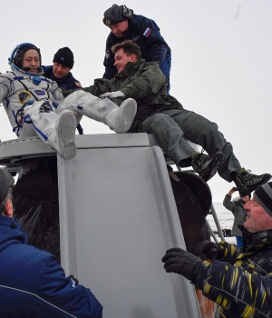 Ground personnel help Alexander Misurkin of Russia to get out of the Soyuz MS-06 space capsule after landing in a remote area outside the town of Dzhezkazgan