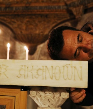 A worshipper places his head on an altar in the Church of the Holy Sepulchre in Jerusalem's Old City
