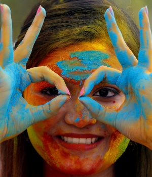 A student of Rabindra Bharati University, with her face smeared in coloured powder, poses during celebrations for Holi inside the university campus in Kolkata