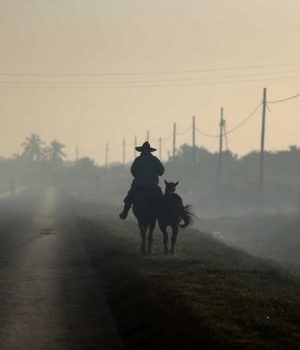 A man rides horseback along a road near Colon