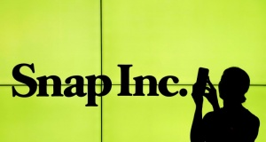 A woman stands in front of the logo of Snap Inc. on the floor of the New York Stock Exchange in New York City
