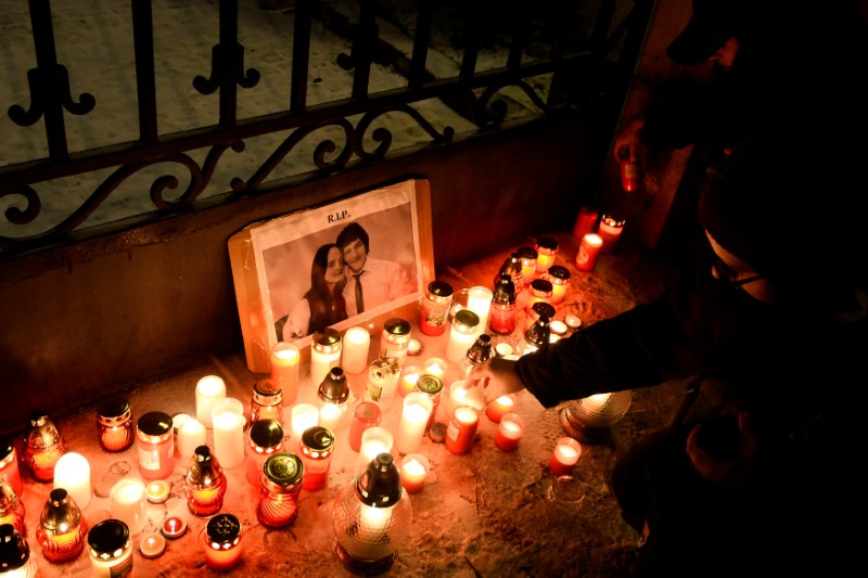 People light candles in front of the Government of the Slovak Republic's building during march in honour of murdered Slovak investigative reporter Jan Kuciak in Bratislava
