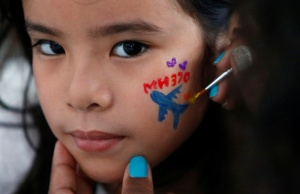 Girl gets face painted during fourth annual remembrance event for missing MH370, in Kuala Lumpur