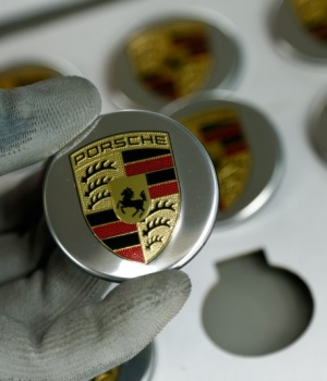 An employee of German car manufacturer Porsche displays a badge depicting a Porsche logo at the Porsche factory in Stuttgart-Zuffenhausen
