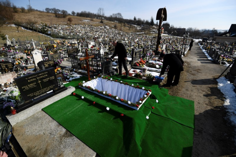 Members of funeral staff prepare a grave before the funeral of investigative reporter Jan Kuciak, who was murdered along with his fiance Martina Kusnirova, at the cemetery in the village of Stiavnik
