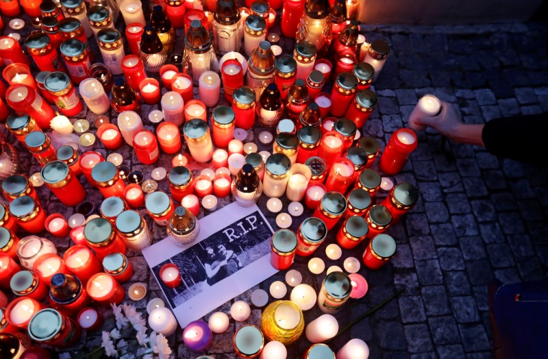 A woman places a candle in memory of killed investigative reporter Jan Kuciak in front of the Slovak embassy in Prague