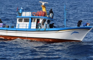 """Crew members are seen at the prow of the fishing boat """"Celine Star"""" with hands behind their heads as Hellenic Coast Guard Special Forces search the vessel at open sea"""