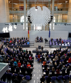 Members of German government and parliament stand as they sing the national anthem during a session of the lower house of parliament Bundestag in Berlin