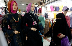 Woman wearing full-face veil shops for clothes in traditional textile market in Jakarta