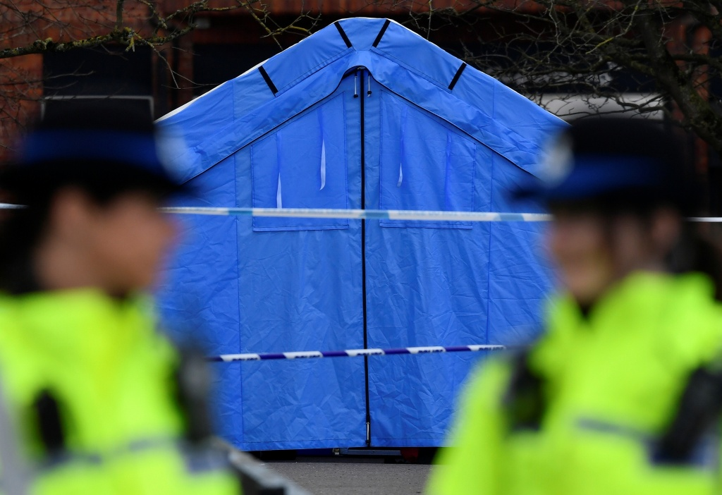 Police officers stand guard in front of a forensics tent in a cordoned off area in the centre of Salisbury