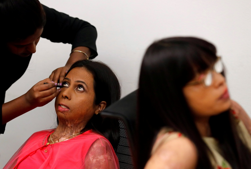 An acid attack survivor has her makeup done backstage as others wait prior to a fashion show to mark International Women's Day in Thane on the outskirts of Mumbai