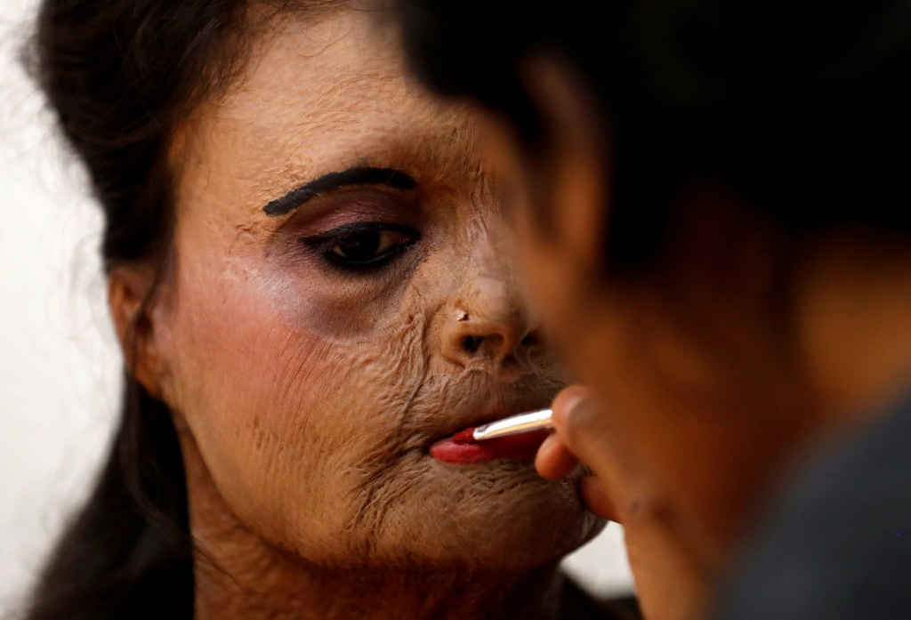 An acid attack survivor has her makeup done backstage prior to a fashion show to mark International Women's Day in Thane on the outskirts of Mumbai