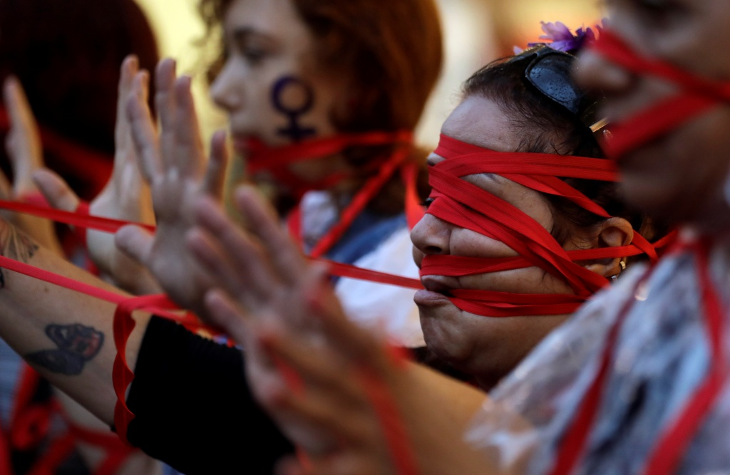 People wear red ribbons on their faces during a demonstration as part of International Women's Day in Sao Paulo