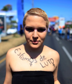 "An activist with the phrase ""We are in Mourning"" written over her body takes part in a march to mark International Women's Day in Managua"