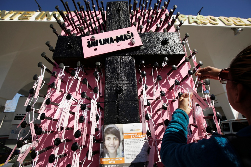 "Woman places names of missing girls at a memorial with a message that reads ""Not One More"", marking the women who have gone missing or found dead, during a protest to mark International Women's Day in Ciudad Juarez"