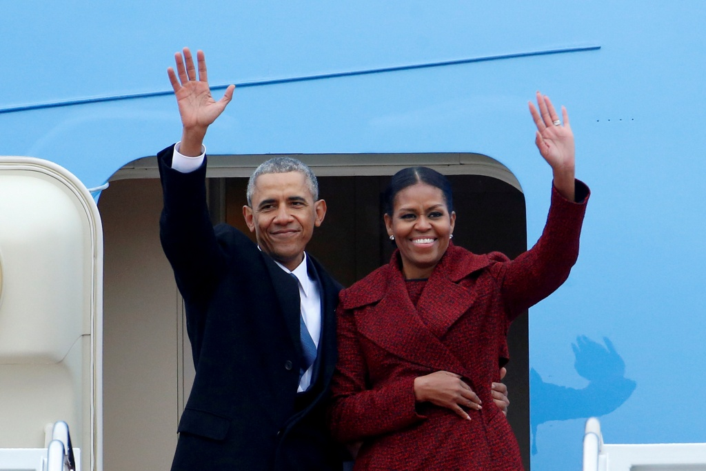 Former President Barack Obama waves with his wife Michelle as they board a Boeing 747 at Joint Base Andrews