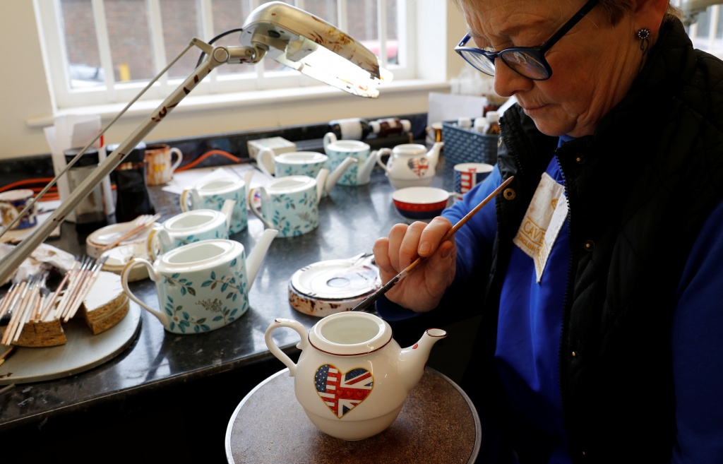 Sue Carter gilds a mug made to celebrate the Royal Wedding between Prince Harry and Meghan Markle at Halcyon Days' Caverswall factory in Stoke-on-Trent