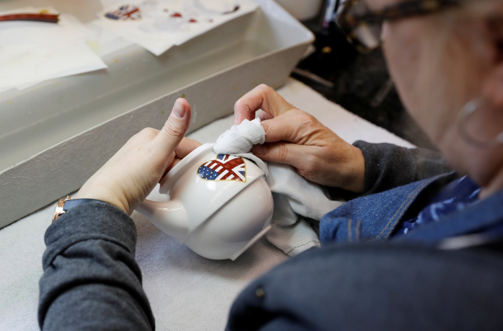 A worker puts a heart on to a teapot made to celebrate the Royal Wedding between Prince Harry and Meghan Markle at Halcyon Days' Caverswall factory in Stoke-on-Trent