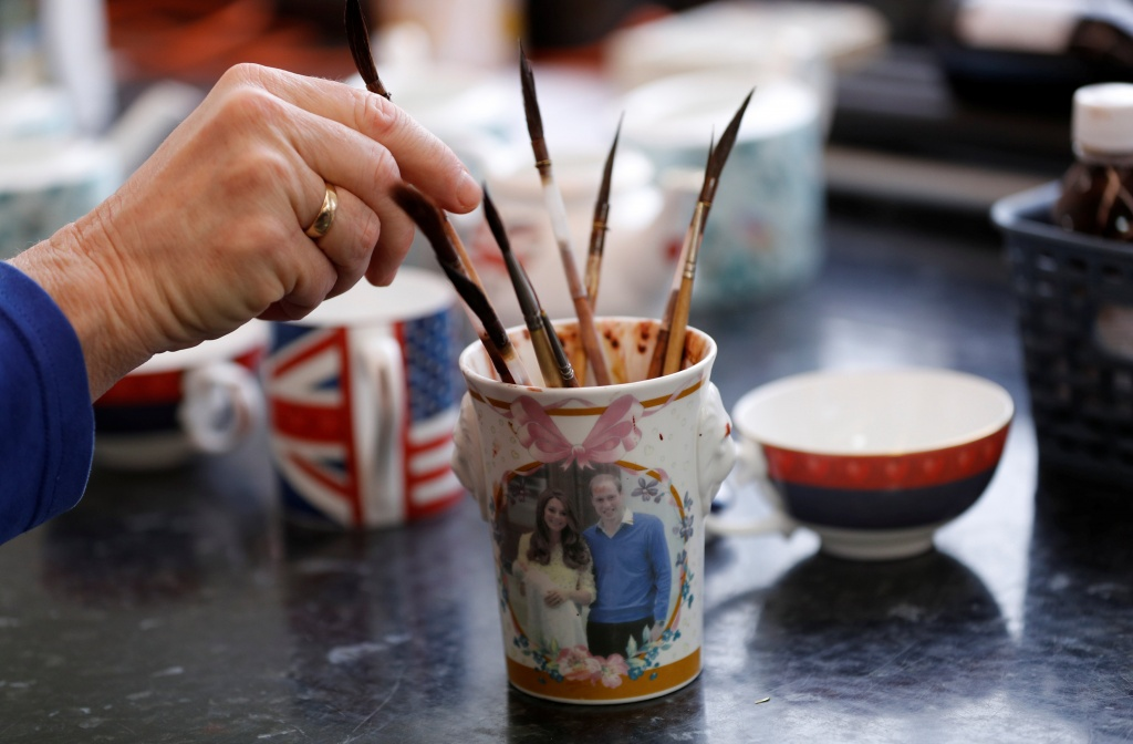 Sue Carter places a brush into a cup depicting the Duke and Duchess of Cambridge whilst gilding pottery to celebrate the Royal Wedding between Prince Harry and Meghan Markle at Halcyon Days' Caverswall factory in Stoke-on-Trent