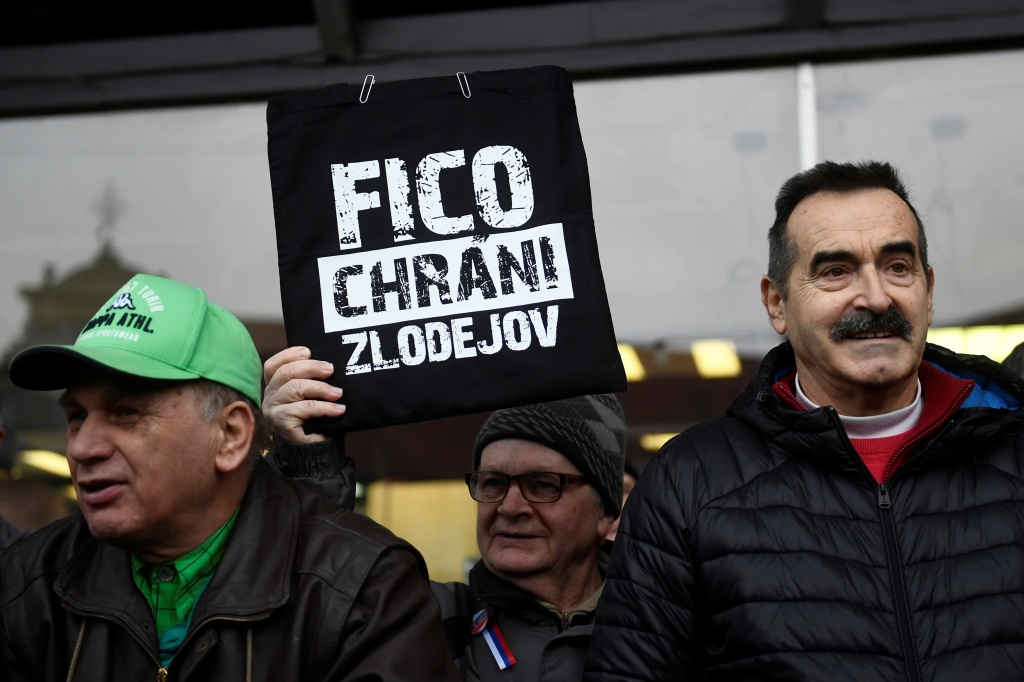 "Demonstrator holds a placard reading ""Fico protects thieves"" during a protest called ""Let's stand for decency in Slovakia"", in Bratislava"
