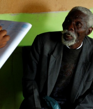 Former gold miner Senzele Silewise, 81, talks to paralegals in Bizana