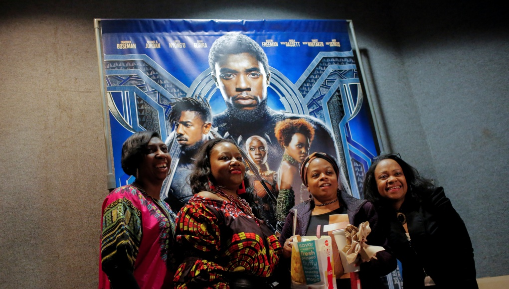 A group of women pose for a photo in front of a poster advertising the film